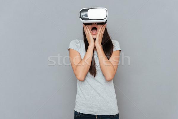 Shocked woman using virtual reality device Stock photo © deandrobot