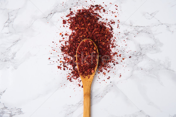 Red hot chilli pepper flakes in wooden spoon Stock photo © deandrobot