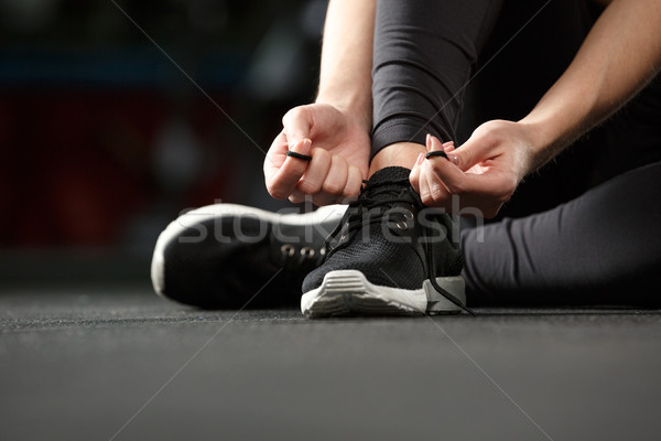 Cropped image of fitness lady tie laces in gym. Stock photo © deandrobot