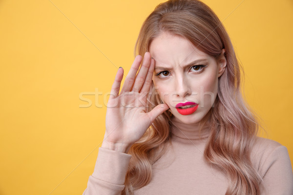 Confused sad young blonde lady with bright makeup lips Stock photo © deandrobot