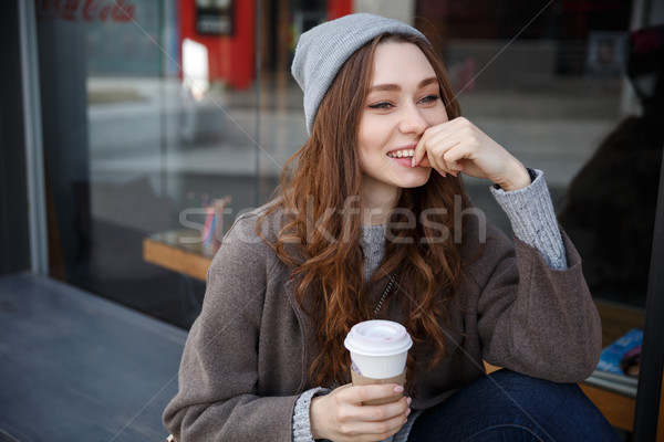 Happy woman drinking coffee-to-go and thinking in the city Stock photo © deandrobot