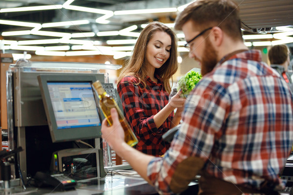 Stock photo: Smiling young lady standing in supermarket shop