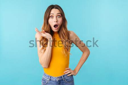 Serious woman standing isolated over blue background Stock photo © deandrobot