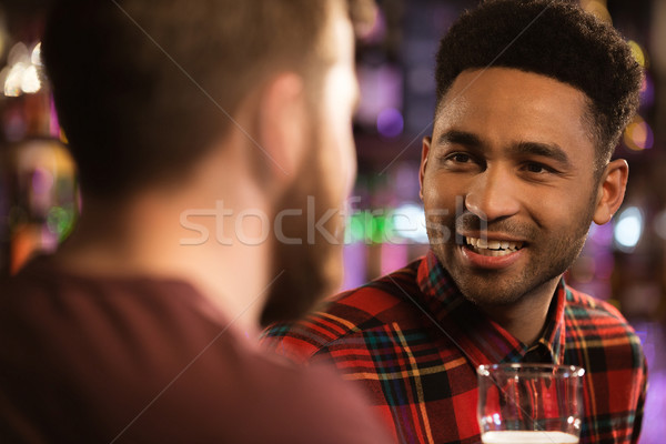 Two happy male friends drinking beer at bar Stock photo © deandrobot