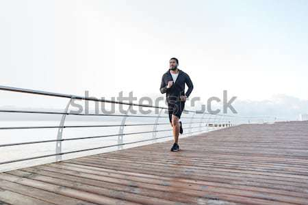 Back view full length portrait of a young sportsman running Stock photo © deandrobot