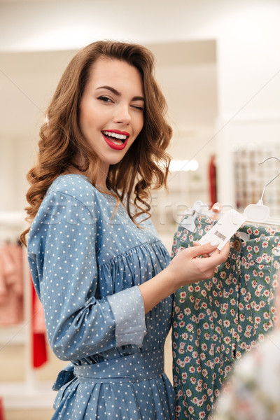 Smiling young lady standing in clothes shop choosing skirt Stock photo © deandrobot