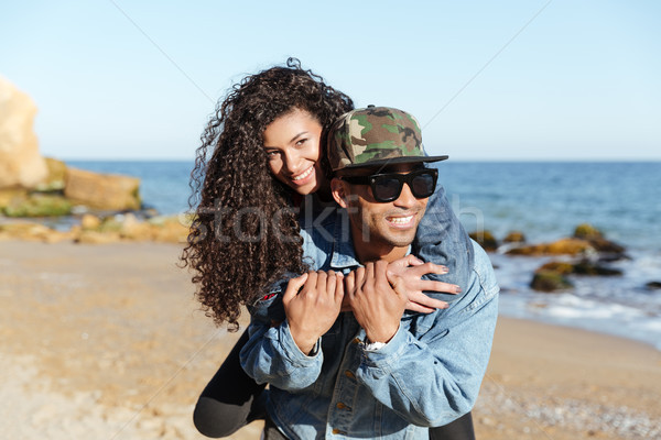 Happy african loving couple walking outdoors at beach Stock photo © deandrobot