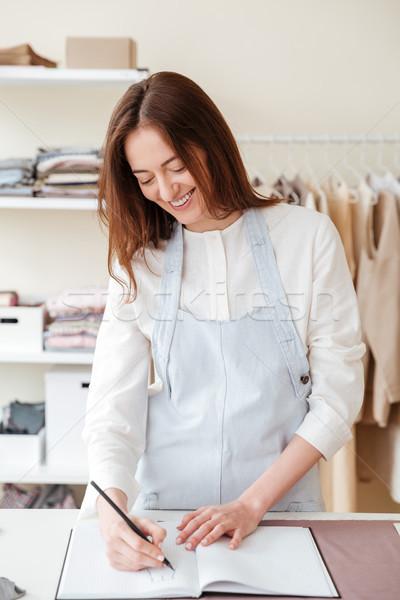 Smiling woman designing in workshop Stock photo © deandrobot