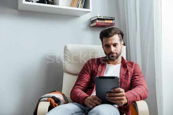Concentrated young bearded man using tablet computer Stock photo © deandrobot