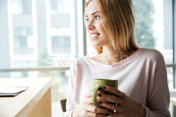 Happy lady in office coworking drinking tea Stock photo © deandrobot