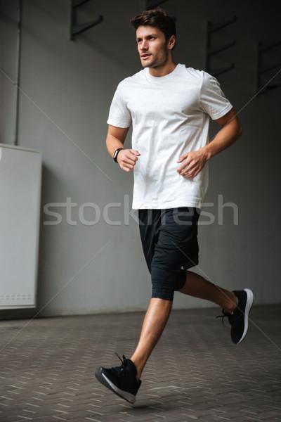 Bonito jovem esportes homem corrida estádio Foto stock © deandrobot