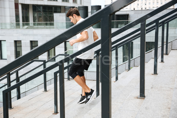 Side view of a sporty athlete man running downstairs Stock photo © deandrobot