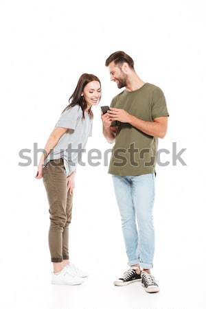 Woman looking in man's smartphone Stock photo © deandrobot