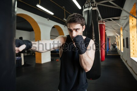 Young man boxer training with punchbag Stock photo © deandrobot