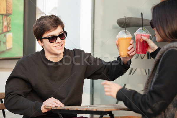 Happy young lady sitting outdoors with her brother drinking juice. Stock photo © deandrobot