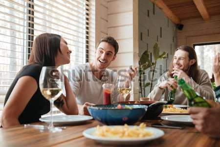 Group of young people saying cheers and eating healthy meals Stock photo © deandrobot