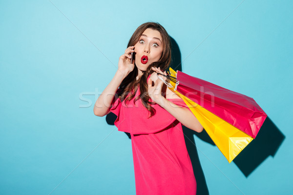 Shocked young brunette lady holding shopping bags talking by phone. Stock photo © deandrobot