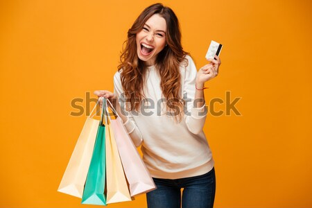 Stock photo: Smiling young brunette woman holding shopping bags chatting by phone.