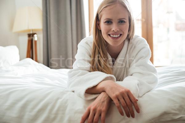 Pretty blonde woman in bathrobe looking camera Stock photo © deandrobot