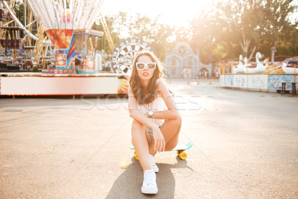 Amazing young woman sitting on skateboard outdoors. Stock photo © deandrobot