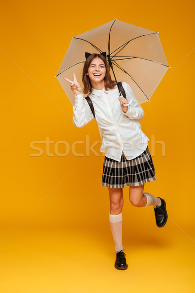 Portrait of a funny happy schoolgirl in uniform holding umbrella Stock photo © deandrobot