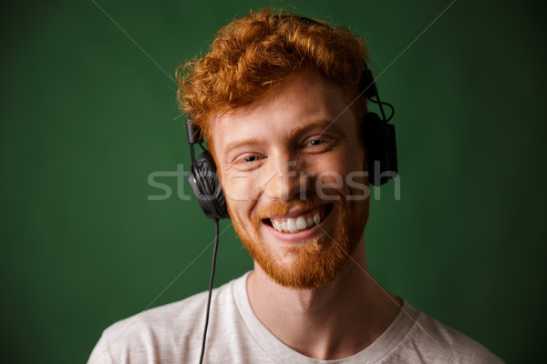 Young readhead man listening music in headphones, looking at cam Stock photo © deandrobot