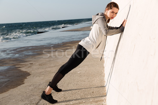 Full-length photo of  fit girl doing push-ups while standing nea Stock photo © deandrobot
