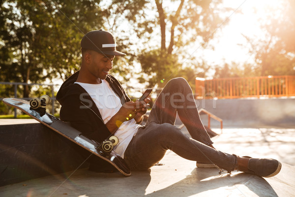 Young african man with a skateboard using smartphone Stock photo © deandrobot