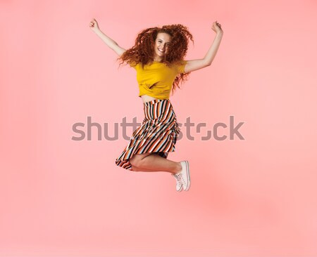 Young happy funny woman in casual clothes jumping isolated Stock photo © deandrobot