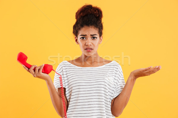 Displeased unhappy lady holding red handset while standing isolated Stock photo © deandrobot