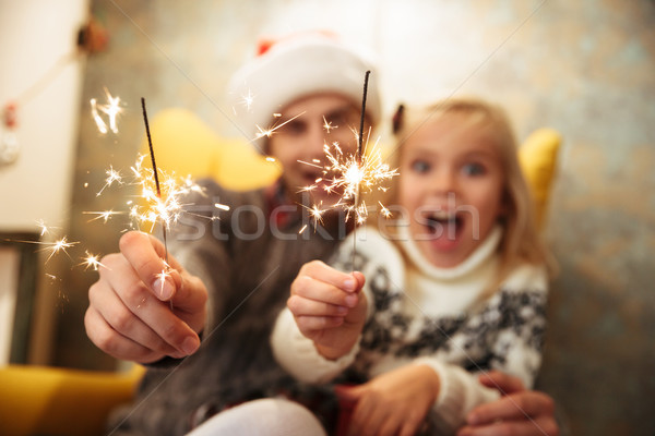 Close-up photo of overjoyed father in Santa's hat and his pretty Stock photo © deandrobot