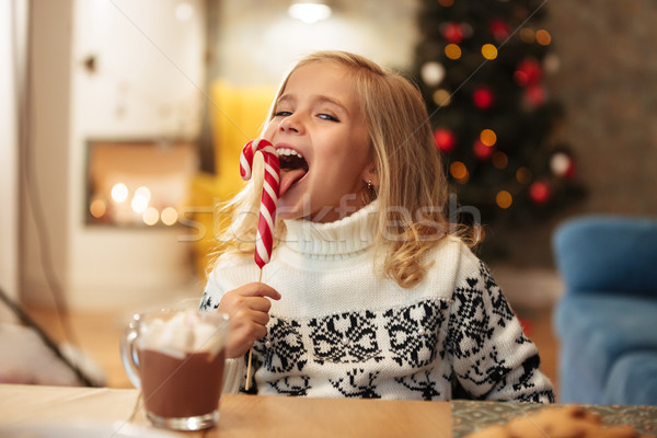 Close-up photo of funny little girl licks candy cane, looking at Stock photo © deandrobot
