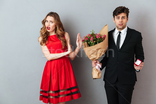 Portrait of a frustrated man proposing to a girl with flowers Stock photo © deandrobot