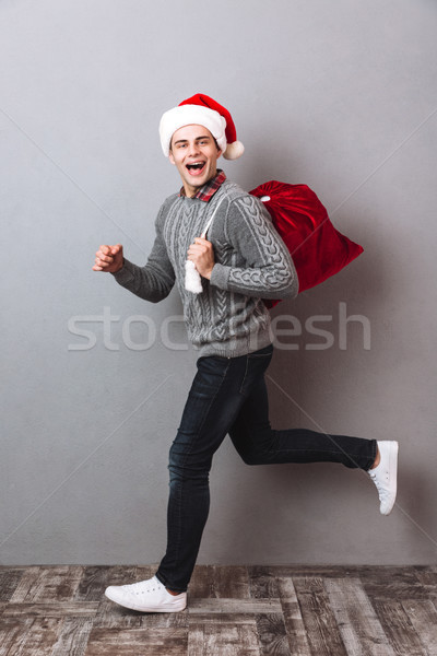 Full length side view image of happy man in sweater Stock photo © deandrobot