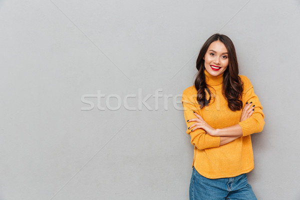Pleased woman in sweater with crossed arms looking at camera Stock photo © deandrobot