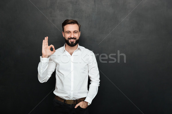 Photo of unshaved guy in office smiling and gesturing with OK si Stock photo © deandrobot