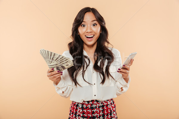 Excited lady holding fan of 100 dollar bills in one hand and tre Stock photo © deandrobot