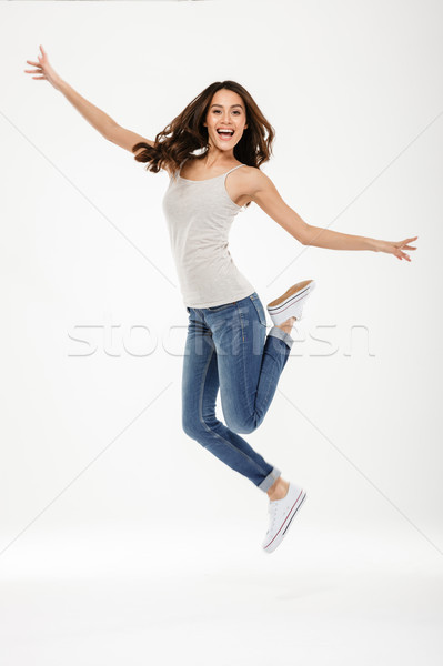 Full length image of Happy brunette woman jumping and rejoices Stock photo © deandrobot