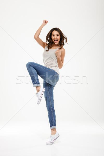 Full length image of Happy brunette woman rejoices Stock photo © deandrobot