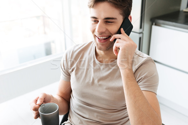 Portrait of cheerful attractive man talking on phone at home Stock photo © deandrobot