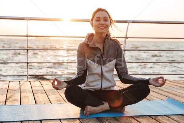 Boldog fiatal lány meditál ül fitnessz víz Stock fotó © deandrobot