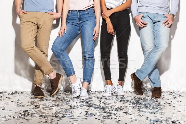 Quattro persone jeans piedi piano confetti isolato Foto d'archivio © deandrobot
