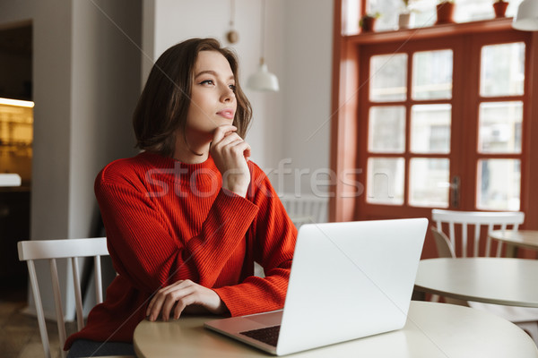 Photo of dreaming young woman 20s in sweater looking aside, whil Stock photo © deandrobot