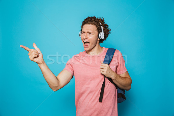 Portrait of university guy 18-20 with curly hair wearing backpac Stock photo © deandrobot
