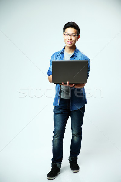 Full length portrait of a happy asian man standing with laptop on gray background Stock photo © deandrobot