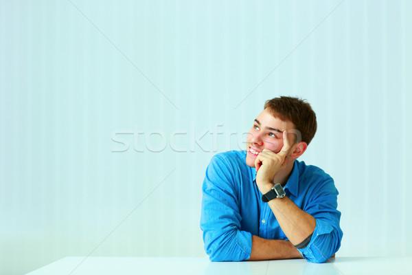 Fiatal üzletember ül asztal felfelé néz iroda Stock fotó © deandrobot