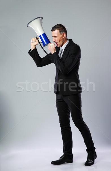 Full length portrait of businessman yelling through megaphone on gray background Stock photo © deandrobot