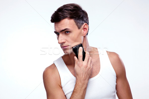 Handsome man shaving with electric razor over gray background Stock photo © deandrobot