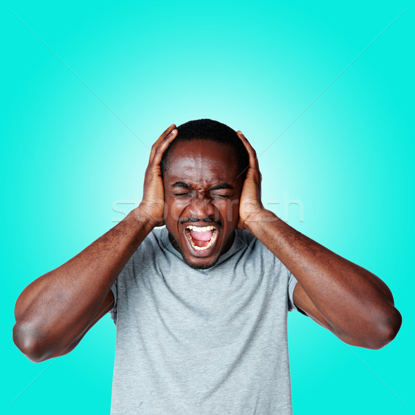 Portrait of african man shouting and closing ear by his hands on blue background Stock photo © deandrobot