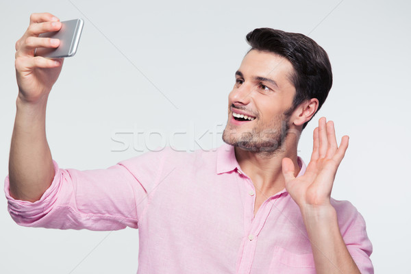 Happy businessman showing greeting sign on smartphone Stock photo © deandrobot